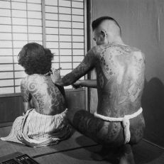 Artist Tattooing Woman's Back